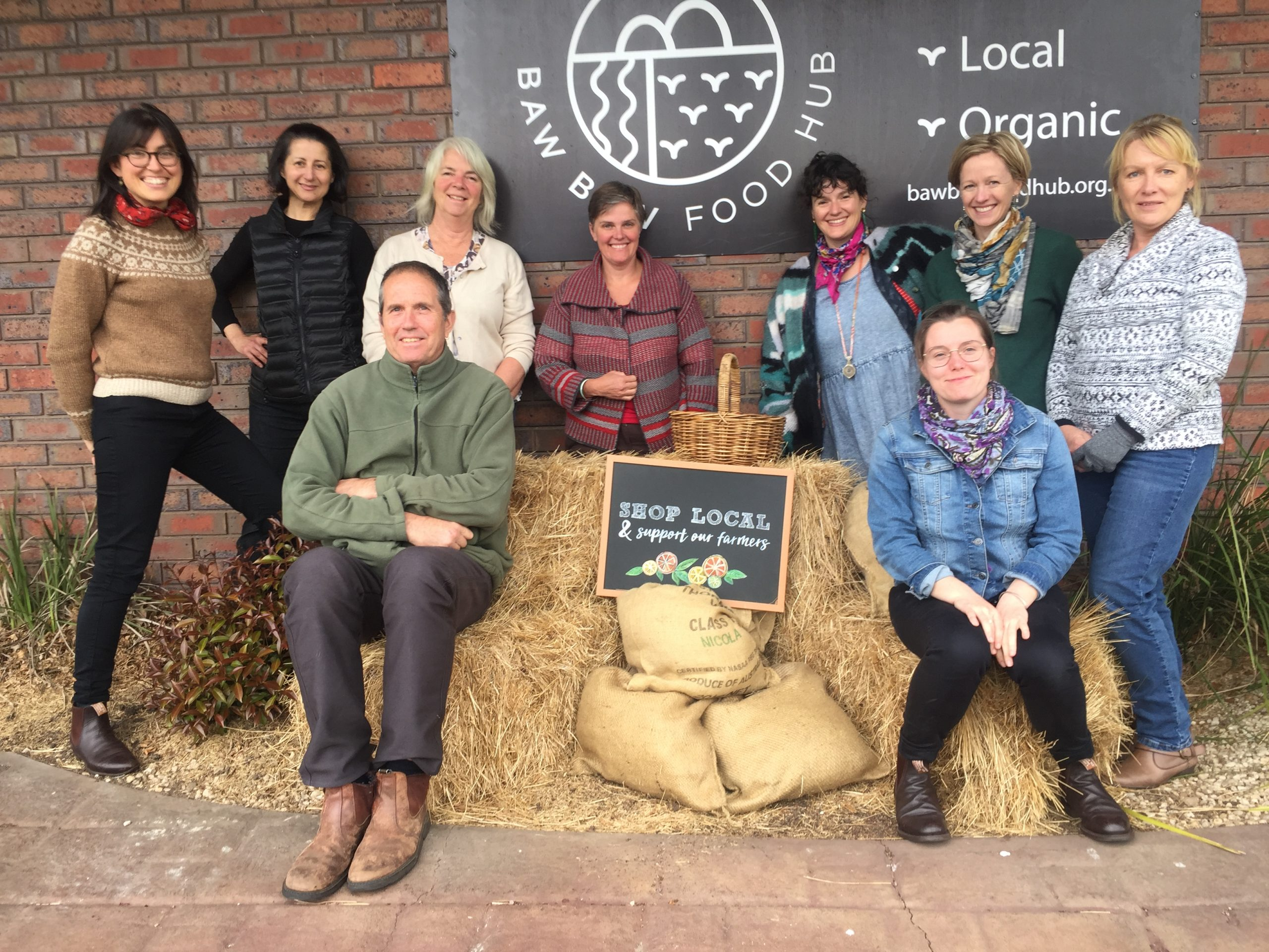a group of people with hay bales in front of a sign for baw baw food hub